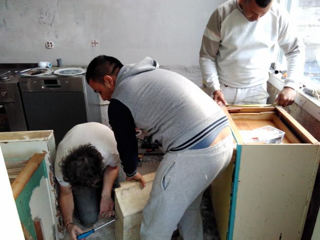 Mannen aan het klussen in de vintage keuken